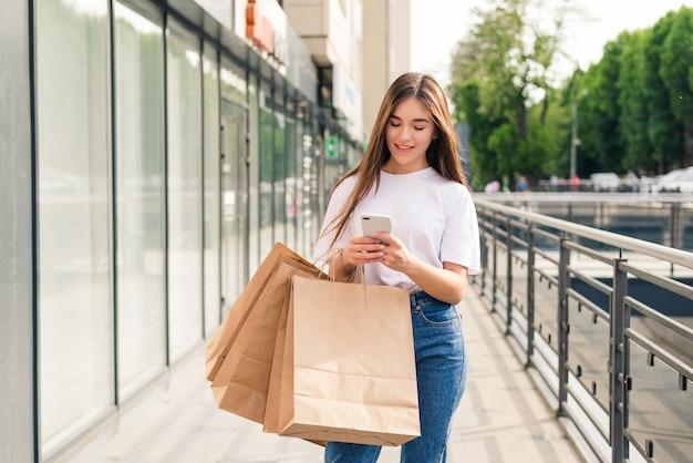 Gute nachrichten mit freunden teilen. nahaufnahme der schönen jungen lächelnden frau, die einkaufstaschen und handy beim stehen im freien hält
