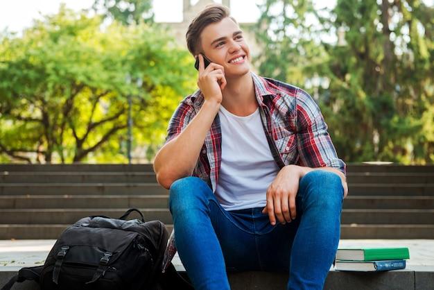 Gute nachrichten von freund. glücklicher männlicher student, der mit dem handy spricht und lächelt, während er an der außentreppe sitzt, mit büchern und rucksack, die in seiner nähe liegen
