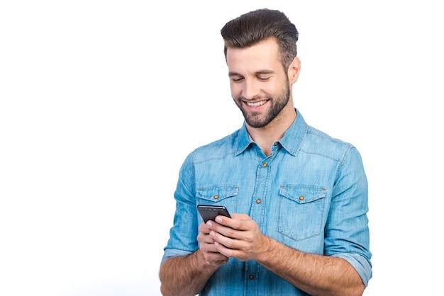 Gute nachrichten von freund. selbstbewusster junger gutaussehender mann in jeanshemd, der ein smartphone hält und es mit einem lächeln betrachtet, während er vor weißem hintergrund steht