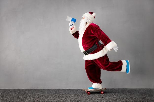 Gute nachrichten weihnachtsmann, der skateboard reitet porträt eines älteren mannes, der weihnachtskostüm trägt