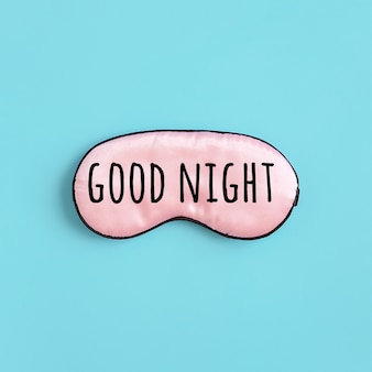 Gute nacht text auf rosa seide schlafmaske für augen auf blauem hintergrund. draufsicht flache lage. konzept augenschutz für guten schlaf und melatonin