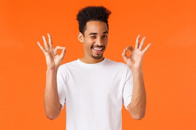 Gute, perfekte wahl. netter, freundlicher und glücklicher lächelnder afroamerikanerkerl im weißen t-shirt, sich versichert fühlend, pelased mit guter entscheidung, wink und okay guter geste der show, orange wand