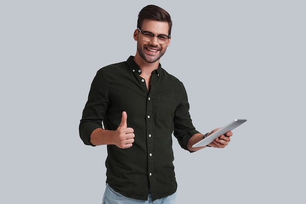 Gute rückmeldungen erhalten. gut aussehender junger mann mit brille, der sein digitales tablet hält und gestikuliert, während er vor grauem hintergrund steht