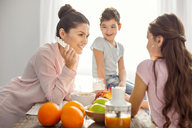 Gute vitamine. attraktive lächelnde dunkelhaarige junge mutter, die vitamine hält und mit ihren kindern über das gesundheitswesen und den jungen spricht, der auf dem tisch sitzt