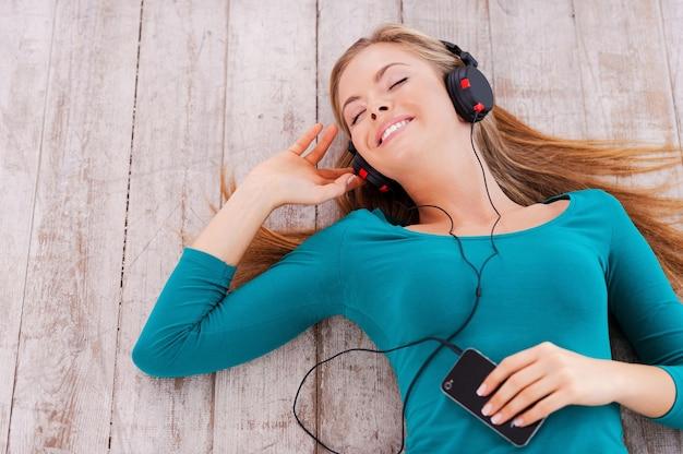 Gute zeit mit mir. draufsicht einer schönen jungen frau, die in ihrer wohnung auf dem boden liegt und musik über kopfhörer hört