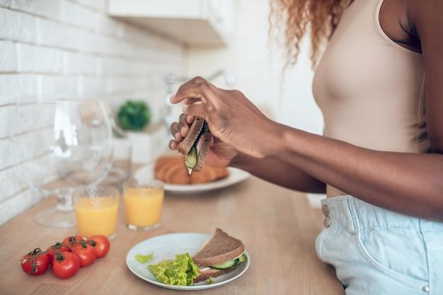 Guten appetit. dünne ordentliche hände der dunkelhäutigen schlanken frau, die frisch zubereitetes sandwich über küchentisch hält
