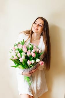 Guten morgen! attraktive junge frau mit langen haaren und strauß weißer und rosa tulpen verbringt zeit zu hause.