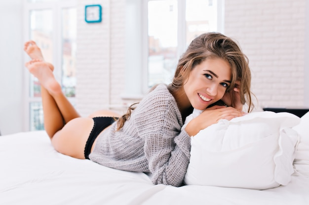 Guten morgen, aufwachen von attraktiver junger frau in strickpullover und schwarzem bikini. schönes mädchen mit dem langen brünetten haar, das auf bett in der modernen wohnung kühlt. lächeln, vergnügen, wahre gefühle.