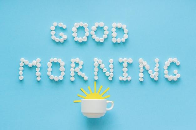 Guten morgen aus marshmallow und kaffeetasse mit aufgehender sonne