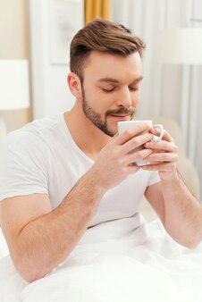 Guten morgen beginnt mit kaffee. schöner junger mann, der eine kaffeetasse in der nähe des gesichts hält und die augen geschlossen hält, im bett frühstückt und lächelt