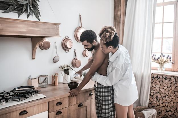 Guten morgen. dunkelhäutige junge frau im hemd umarmt ihren hemdlosen ehemann, der das frühstück am morgen in der küche vorbereitet
