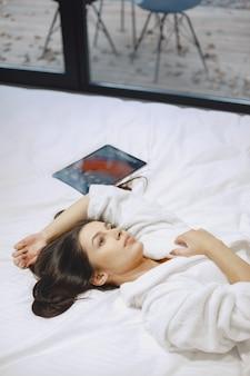 Guten morgen. frau in einem bett. dame im schlafzimmer. brünette mit tablette.