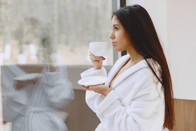 Guten morgen. frau trinkt kaffee. dame am fenster.