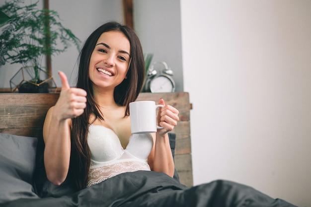 Guten morgen frau wachte im bett auf. trinkender kaffee der frau im bett