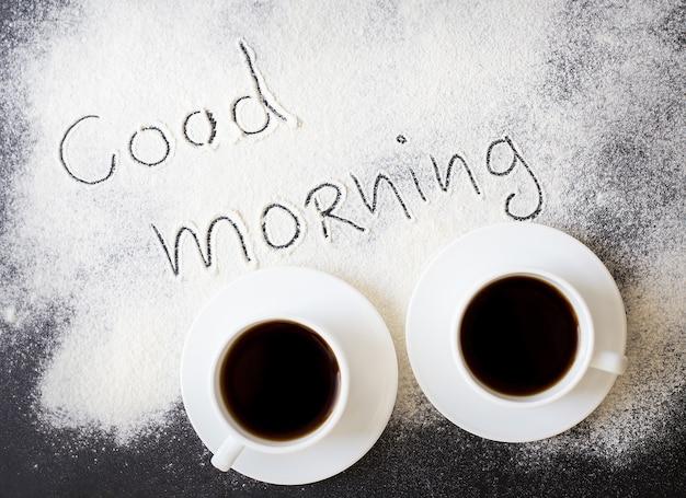 Guten morgen inschrift auf dem brett mit mehl und zwei tassen kaffee