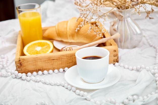 Guten morgen. kontinentales frühstück auf weißen bettlaken.