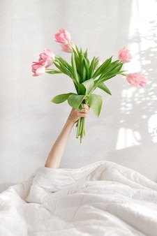 Guten morgen rosa tulpen in einer frauenhand