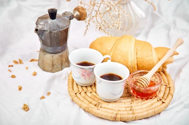 Guten morgen. zwei tasse kaffee mit croissant und marmelade.