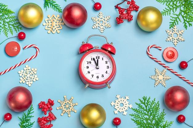 Guten rutsch ins neue jahr-ebene legen zusammensetzung, uhr weihnachtsdekor auf blauem hintergrund