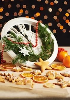 Guten rutsch ins neue jahr um mitternacht, alte hölzerne uhr mit lichterketten und tannenzweigen. weihnachtslebkuchenplätzchen und gebratene orange scheiben kochen und verzierend