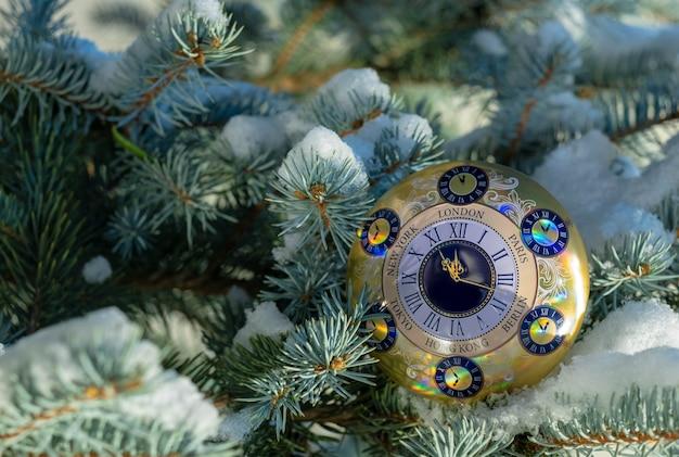 Guten rutsch ins neue jahr und frohe weihnachten, weihnachtshintergrundwecker auf dem weihnachtsbaum.