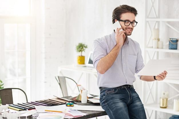 Guten tag. attraktiver glücklicher mann, der am telefon spricht und ein blatt papier hält