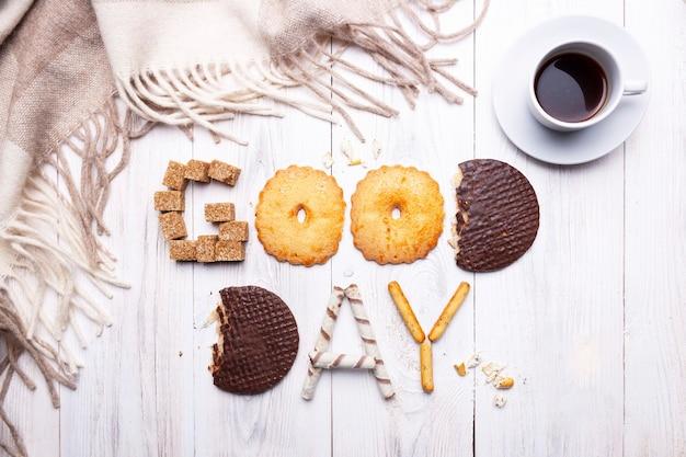 Guten tag besteht aus keksen, schokolade, zucker, süßen strohhalmen, einer tasse schwarzem kaffee