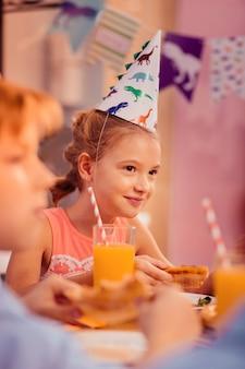 Guten tag. fröhliches mädchen, das lächeln auf ihrem gesicht hält, während pizza essen geht