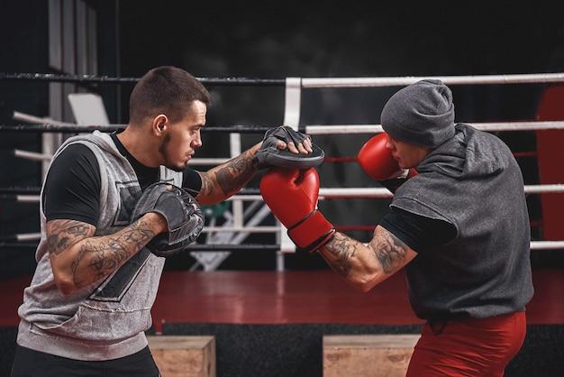 Guter aufwärtshaken zur pfotenseitenansicht des muskulösen athleten in boxhandschuhen beim training