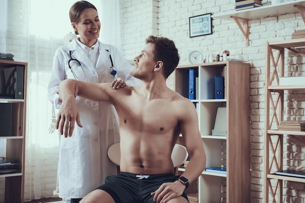 Guter doktor überprüft den arm des athleten.