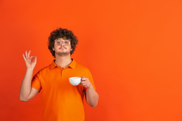 Guter kaffee, freut mich. das monochrome portrait des kaukasischen jungen mannes auf oranger wand. schönes männliches lockiges modell im lässigen stil.
