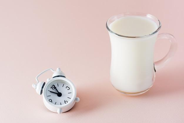 Guter schlaf. ein glas milch ein produkt zum guten einschlafen und ein wecker auf einem rosa hintergrund. abendritual