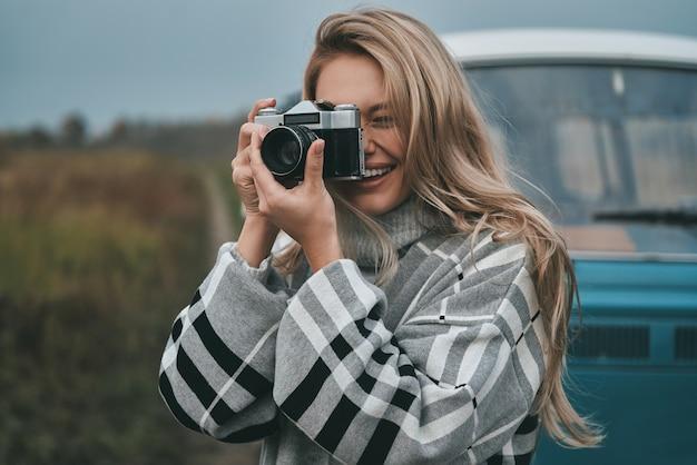 Guter schuss! attraktive junge frau, die fotografiert und lächelt, während sie draußen mit dem blauen retro-stil-minivan steht