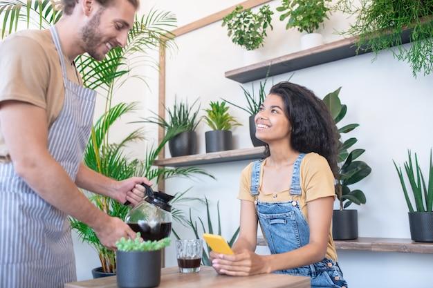 Guter service, cafe. junger erwachsener freundlicher mann in der gestreiften schürze, die kaffee von kaffeekanne zu lächelnder frau gießt, die im café sitzt