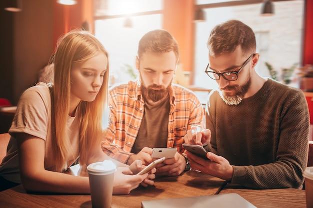 Gutes bild von drei konzentrierten freunden, die zusammen am tisch sitzen und auf ihre telefone schauen. sie spielen spiele.