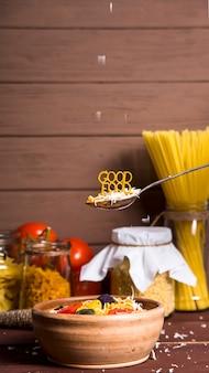 Gutes essen wird mit teigwaren auf einem löffel neben einem teller ausgekleidet