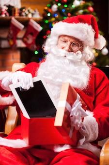 Gutes geschenk! der fröhliche weihnachtsmann legt ein digitales tablet in die geschenkbox und lächelt, während er an seinem stuhl mit weihnachtsbaum im hintergrund sitzt