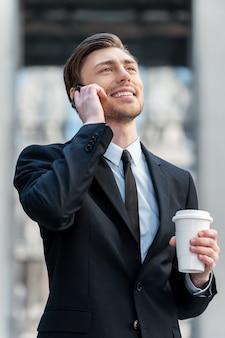 Gutes gespräch. fröhlicher junger mann, der am handy spricht und seinen kaffee hält