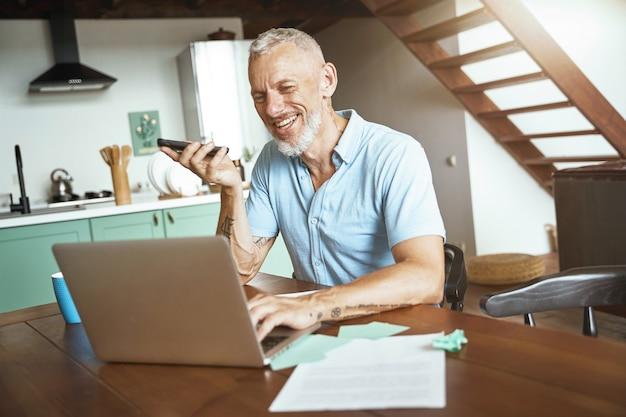 Gutes gespräch glücklicher kaukasischer mann mittleren alters, der beim sitzen am tisch und beim arbeiten telefoniert
