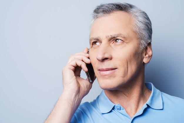 Gutes gespräch. porträt eines selbstbewussten älteren mannes im hemd, der am handy spricht und lächelt, während er vor grauem hintergrund steht