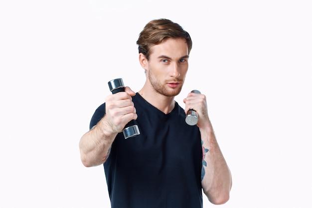 Guy athlet in einem schwarzen t-shirt mit hanteln in den händen