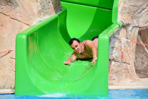 Guy auf wasserrutsche im sommer urlaub