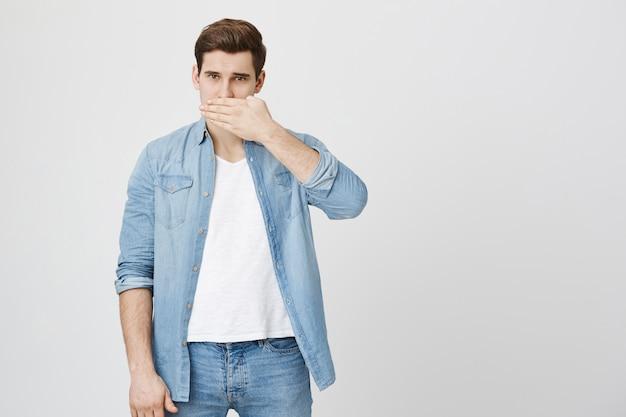 Guy bedeckt den mund und schweigt