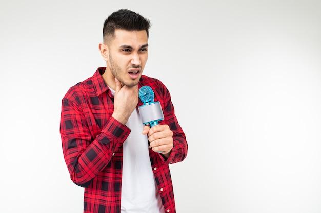 Guy bereitet eine rede vor, die ein mikrofon in seiner hand auf einem weiß hält, das mit kopienraum isoliert wird