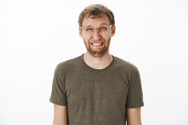Guy blinzelt und macht ein lustiges gesicht, das saure zitrone mit gerunzelter stirn und faltiger nase isst und angewidert und unzufrieden in transparenten gläsern und grünem t-shirt steht