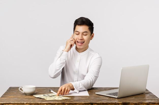 Guy, der die party arrangiert, hat viel geld bekommen, den preis gefeiert und viel geld gewonnen. attraktiver glücklicher und erfreuter wohlhabender asiatischer geschäftsmann im büro, teilhabertelefon anrufend und spielen mit dollar