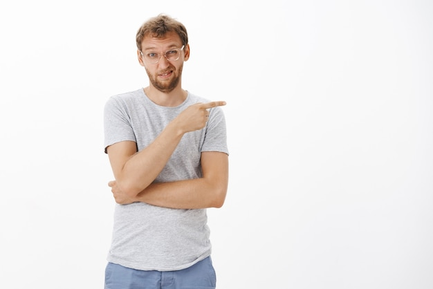 Guy, der versucht, seine abneigung auszudrücken, zeigt höflich das richtige schielen und grimassen vor unzufriedenheit, unbeeindruckt von der schwachen arbeit des teams, das unzufrieden und zweifelhaft steht