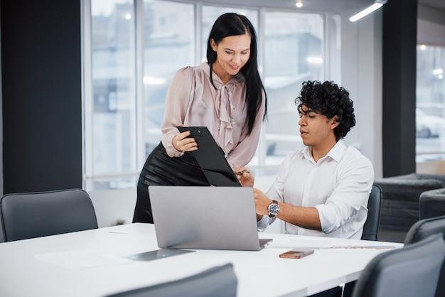 Guy erklären die bedeutung des dokuments. gelockter kerl und brunettemädchen bespricht die details des vertrages im modernen büro