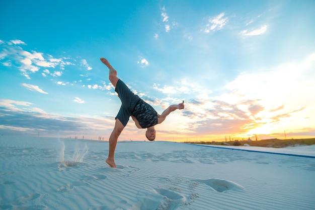 Guy fliegt kopfüber auf sand in der wüste.