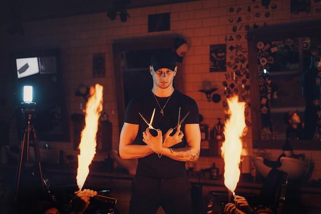 Guy friseur posiert mit schere und flamme